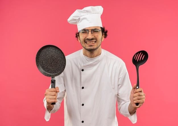 ピンクのフライパンとヘラを保持しているシェフの制服とメガネを身に着けている若い男性料理人を強調