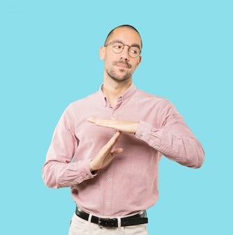 Подчеркнул молодой человек, делая жест тайм-аут своими руками