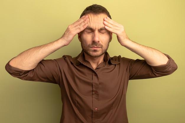 オリーブグリーンの壁に隔離された目を閉じて頭に手を置くストレスの若い男