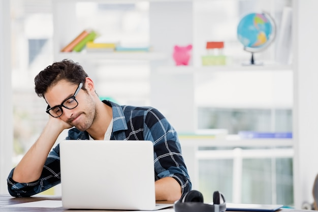 Stressed young man sitting at his desk