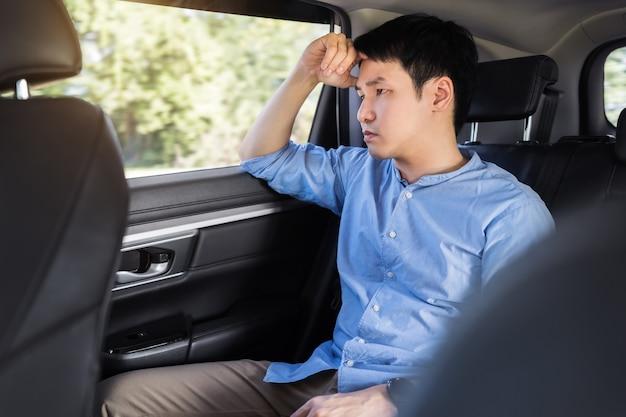 차 뒷좌석에 앉아 스트레스를 받는 청년