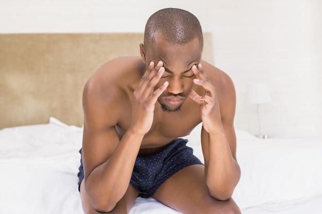 ベッドの上に座っている若い男を強調