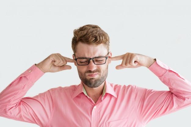 Подчеркнутый молодой человек, останавливающий уши с пальцами