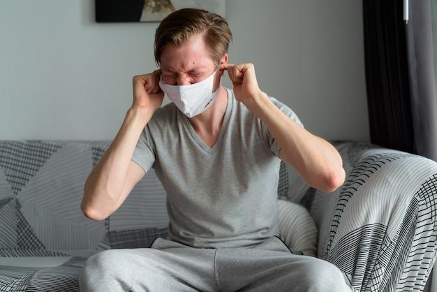 検疫の下で自宅で耳を覆うマスクを持つ若い男を強調