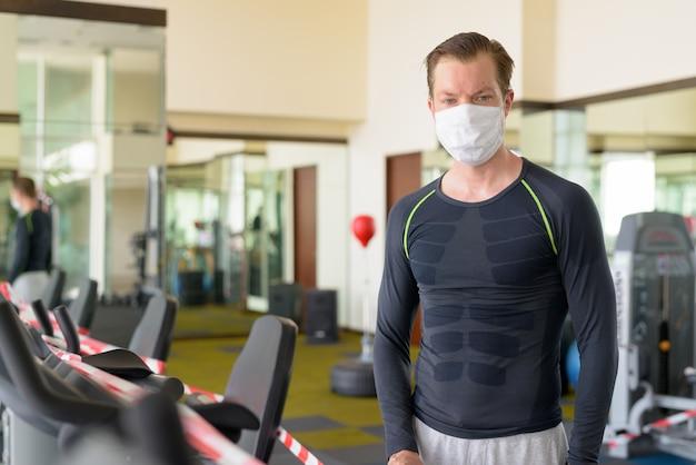 コロナウイルスcovid-19安全測定のために制限された運動器具を見てマスクを持つ若い男を強調