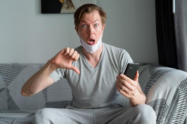 電話を使用し、検疫の下で自宅で親指を下に与えるマスクで若い男を強調
