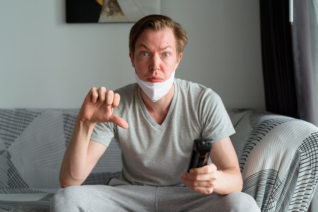 Stressed young man with mask watching tv and giving thumbs down at home under quarantine