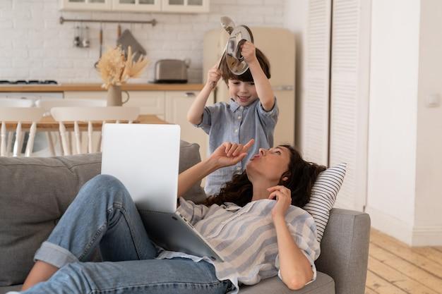 스트레스를 받는 젊은 엄마는 아들에게 일에 집중하려고 진정하라고 요청합니다. 작은 아이는 밀레니얼 엄마를 방해합니다