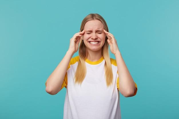 青い背景の上に立っている間カジュアルな服を着て、目を閉じて顔をしかめ、こめかみに指を置いている長い髪の若いきれいな金髪の女性を強調