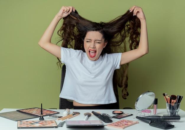 Giovane e graziosa ragazza stressata seduta al tavolo da trucco con strumenti per il trucco che le tirano i capelli con gli occhi chiusi su uno spazio verde oliva