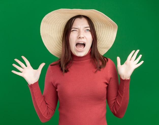 Una giovane ragazza carina stressata che indossa un cappello da spiaggia che guarda in alto mostrando le mani vuote che urlano
