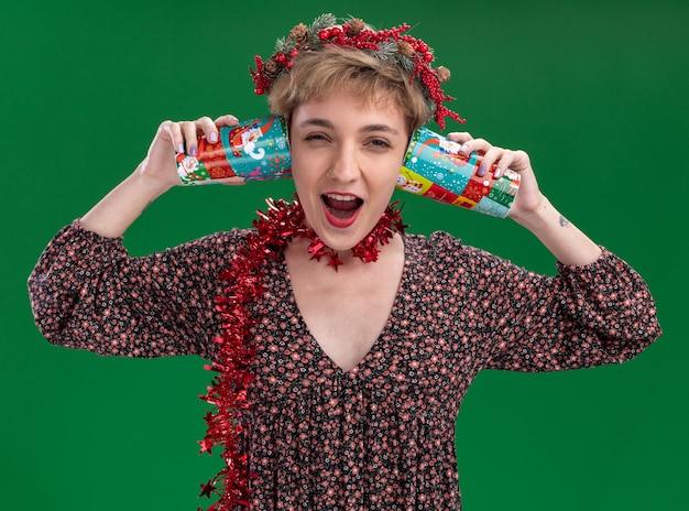 녹색 벽에 고립 된 비명 비밀을 듣고 귀 옆에 플라스틱 크리스마스 컵을 들고 목에 크리스마스 머리 화환과 반짝이 화환을 입고 젊은 예쁜 여자를 강조