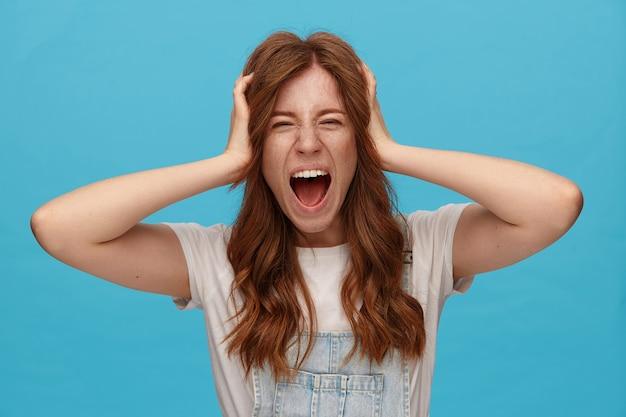 Sottolineato giovane donna graziosa rossa con trucco naturale che tiene la testa con le mani alzate e il viso accigliato mentre urla con la bocca larga aperta, in posa su sfondo blu
