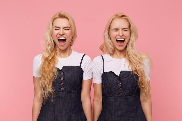 ピンクの背景の上に孤立し、興奮して叫んでいる間、目を閉じて顔をしかめている緩い髪の若いかなり白い頭の女性を強調しました