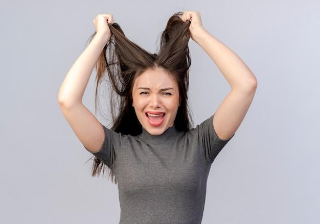 Sottolineato giovane donna graziosa che tira i capelli isolati su sfondo bianco