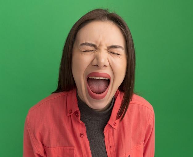녹색 벽에 격리된 눈을 감고 비명을 지르는 젊은 예쁜 여자