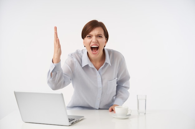 Sottolineato giovane donna bruna dai capelli corti con acconciatura casual gridando con rabbia e sollevando emotivamente la sua mano, vestita in camicia blu mentre posa su bianco