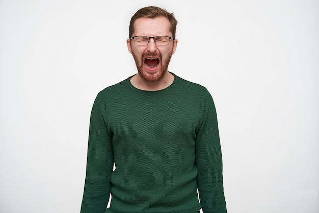 Stressed young short haired brunette man with beard wearing eyewear and green sweater posing with hands down, screaming desperately with closed eyes