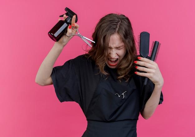 ピンクの背景に分離された目を閉じて叫んでスプレーボトルの櫛とはさみを保持している制服を着ている若いスラブの女性の床屋を強調