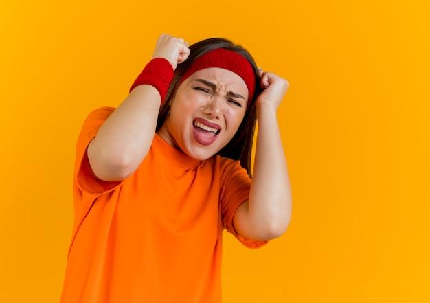 Sottolineato giovane donna sportiva che indossa la fascia e braccialetti toccando la testa con i pugni urlando con gli occhi chiusi