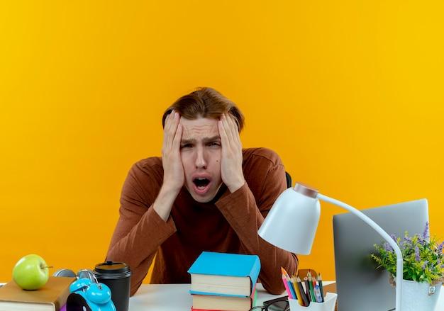 노란색에 뺨에 손을 댔을 학교 도구로 책상에 앉아 젊은 학생 소년을 강조