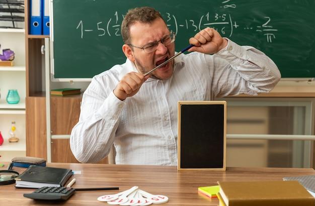 Stressato giovane insegnante con gli occhiali seduto alla scrivania con materiale scolastico e mini lavagna su di esso in aula mordere il puntatore stick