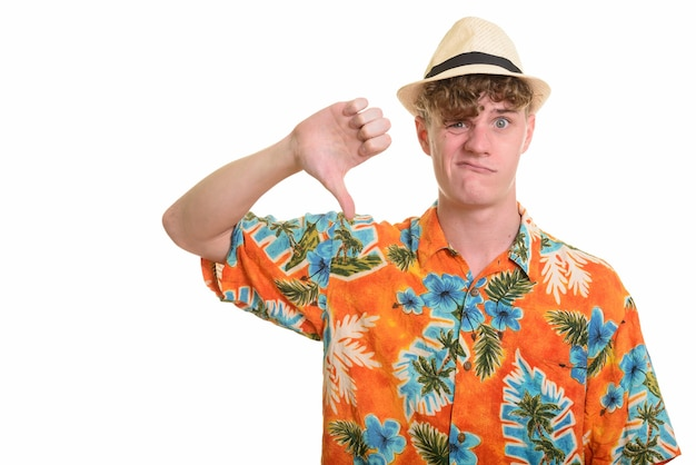 Stressed young tourist man with hat giving thumbs down for vacation