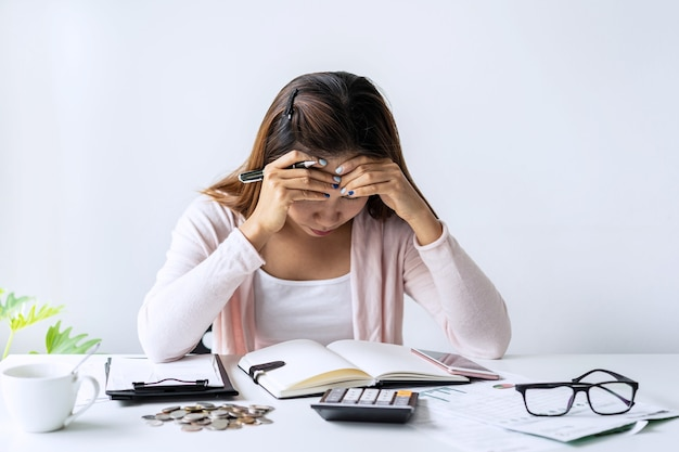 毎月の家の費用を計算する若い女性を強調