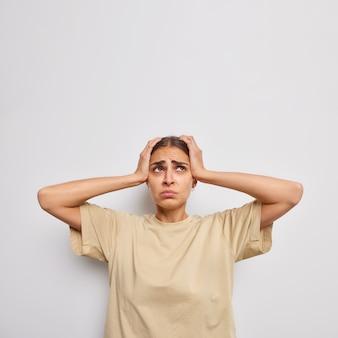 스트레스를 받는 젊은 여성이 슬픈 표정으로 머리를 잡고 흰 벽에 기대어 캐주얼한 베이지색 티셔츠를 입고 편두통을 앓는다