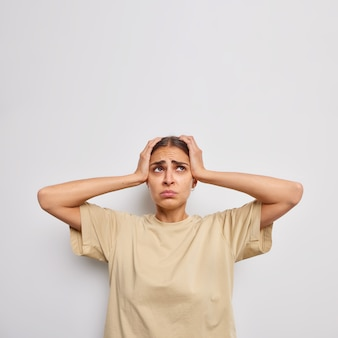 Stressed young woman grabs head focused above with sad expression suffers migraine wears casual beige t shirt poses against white wall