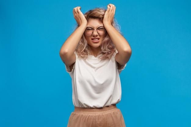 머리를 쥐어 짜는 세련된 안경에 스트레스를받은 젊은 여성은 직장에서 스트레스가 많은 하루 때문에 참을 수없는 두통을 참을 수 없습니다. 고통에서 찡그린 짜증이 좌절 된 여성