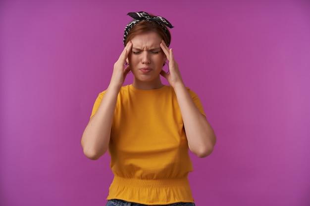 머리띠와 눈을 가진 노란색 티셔츠에 스트레스를받은 젊은 여성은 그녀의 사원을 만지고 보라색 벽에 두통을 겪었습니다.
