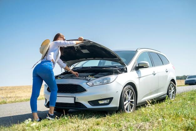彼女の車のエンジンを見ている若い女性を強調しました。ロードトリップの問題。車は修理が必要です。
