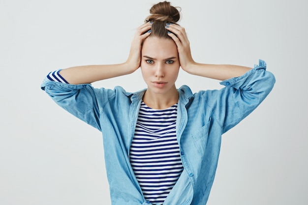 Stressed young woman with both hands on head
