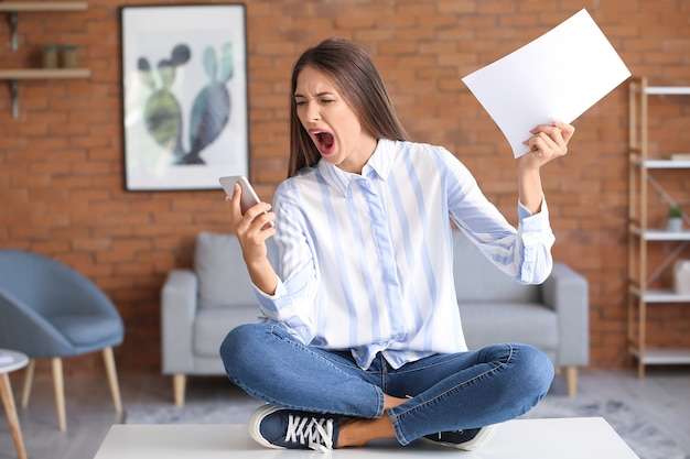 自宅で携帯電話でストレスを抱えた若い女性