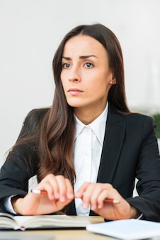 Stresses office female worker holding red pencil with two hands over the desk
