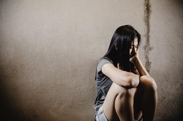 地面に座っているストレスと絶望的な女性。