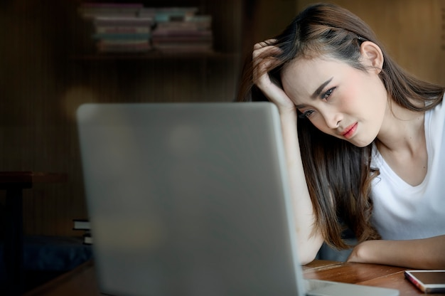 Stressful asian woman sitting in office and looking at laptop screen.