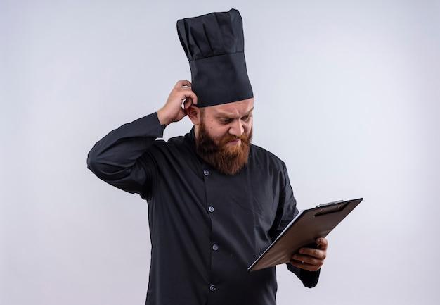 Un uomo chef barbuto stressante in uniforme nera guardando una cartella vuota con la mano sulla testa su un muro bianco