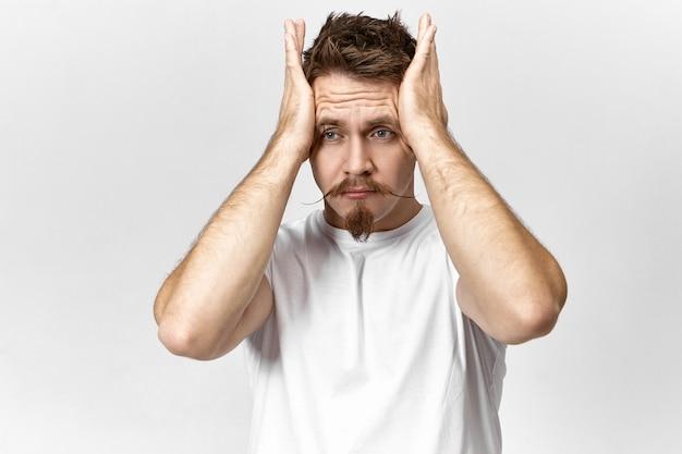 飛行機に遅れるのを忘れっぽい欲求不満の表情をしているストレスの多いあごひげを生やした男。こめかみを絞るスタイリッシュな若い男性の肖像画、ひどい頭痛のために痛みを伴う表情をしています
