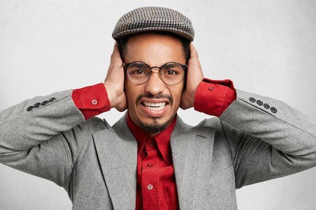 Stressante uomo barbuto con berretto e giacca, copre le orecchie, si protegge dal rumore,