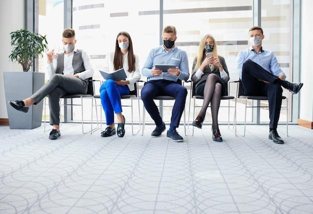 Covid19 영향 동안 얼굴 마스크, 사회적 거리 격리로 면접을 기다리는 스트레스를 받는 사업가들.