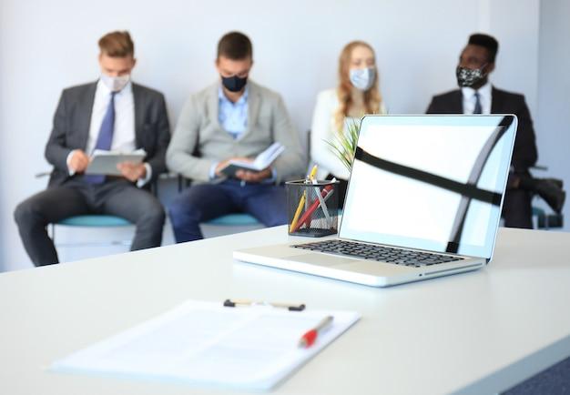 마스크로 면접을 기다리는 스트레스 받는 사업가들, covid19 기간 동안 사회적 거리두기