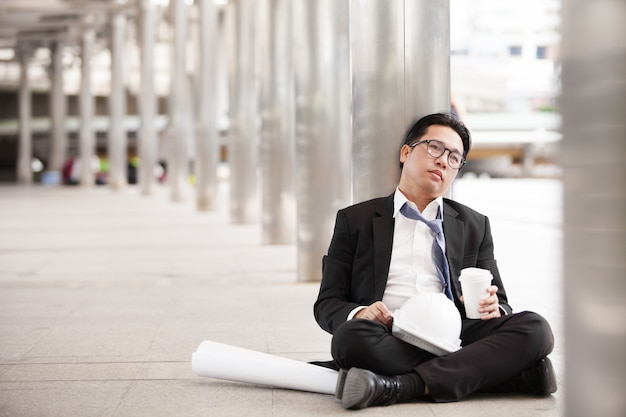 Stressful businessman or engineer sitting outdoor thoughtful thinking with hopeless