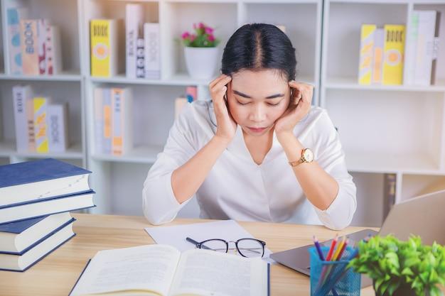 Стрессовая деловая женщина страдает от головной боли от работы в офисе, устала и скучает