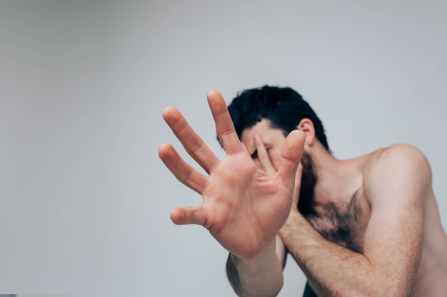 Напряженно смущенный парень показывает руку и пытается спрятаться от камеры. один в комнате в растерянности или настроении. страдает депрессией и психическим заболеванием.