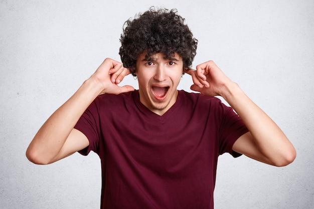 ストレスの多い巻き毛の男性がパニック状態で耳を塞ぎ、大きな刺激的な音を避けます