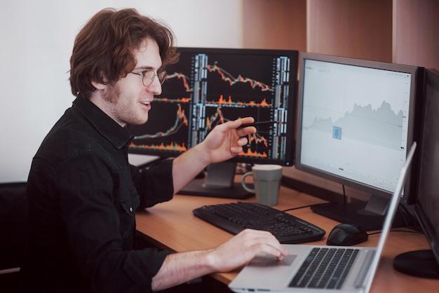 Напряженный день в офисе. молодой бизнесмен держа руки на его стороне пока сидящ на столе в творческом офисе. фондовая биржа трейдинг форекс финансы графическая концепция
