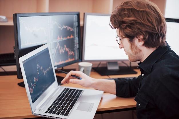 Напряженный день в офисе. молодой бизнесмен держа руки на его стороне пока сидящ на столе в творческом офисе. фондовая биржа трейдинг форекс финансы