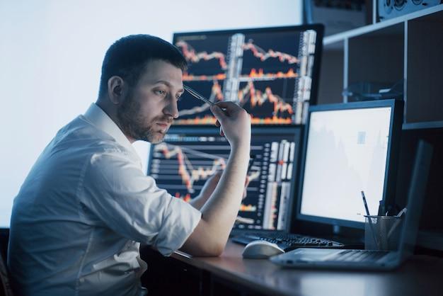 Напряженный день в офисе. молодой бизнесмен держа руки на его стороне пока сидящ на столе в творческом офисе. биржевая торговля форекс финансы графика